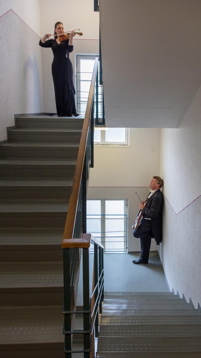 Treppenhaus mit zwei Personen und Geigen
